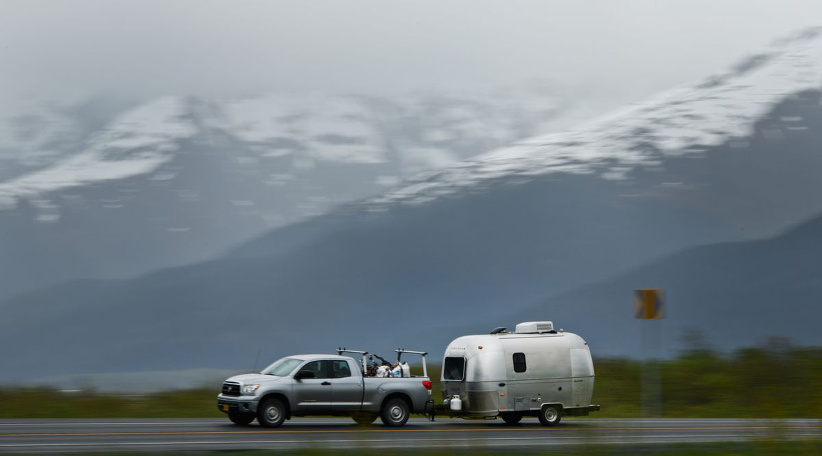 A southbound vehicle on the Seward Highway tows a camper along Turnagain Arm on Thursday ahead of the Memorial Day weekend. (Marc Lester / ADN)