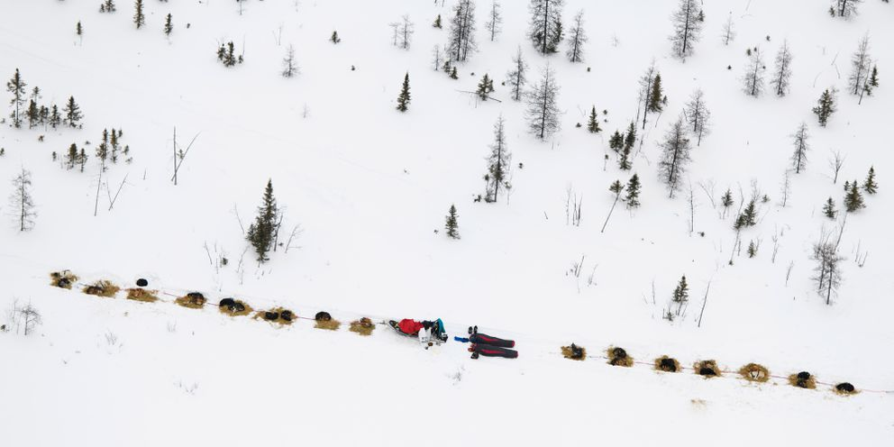 Twin sisters Anna and Kristy Berington rest next to each other on the trail between Rohn and Nikolai during the 2019 race. (Marc Lester / ADN archive)