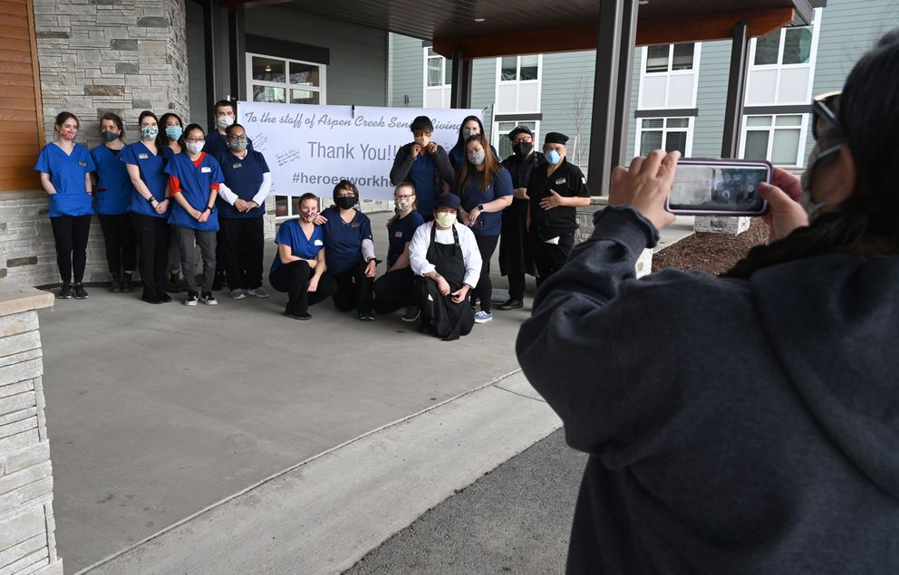 Pheng Scott takes a photo of caretakers and other staff at the Aspen Creek Senior Living facility Wednesday. (Anne Raup / ADN)