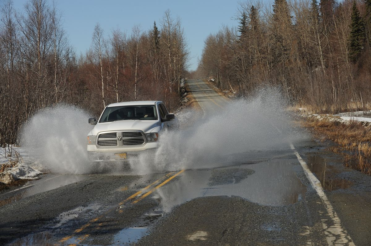 A truck splashes through water on the Old Seward Highway on the backside of Potter Marsh in South Anchorage on Wednesday. (Bob Hallinen / Alaska Dispatch News)