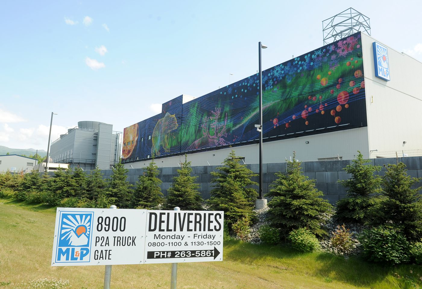 The mural Cosmic Rise covers the side of the Municipal Light and Power's Plant 2A next to the Glenn Highway in Anchorage on July 7. Haddad Drugan of Seattle designed the 1% for Art project. (Bob Hallinen / ADN)