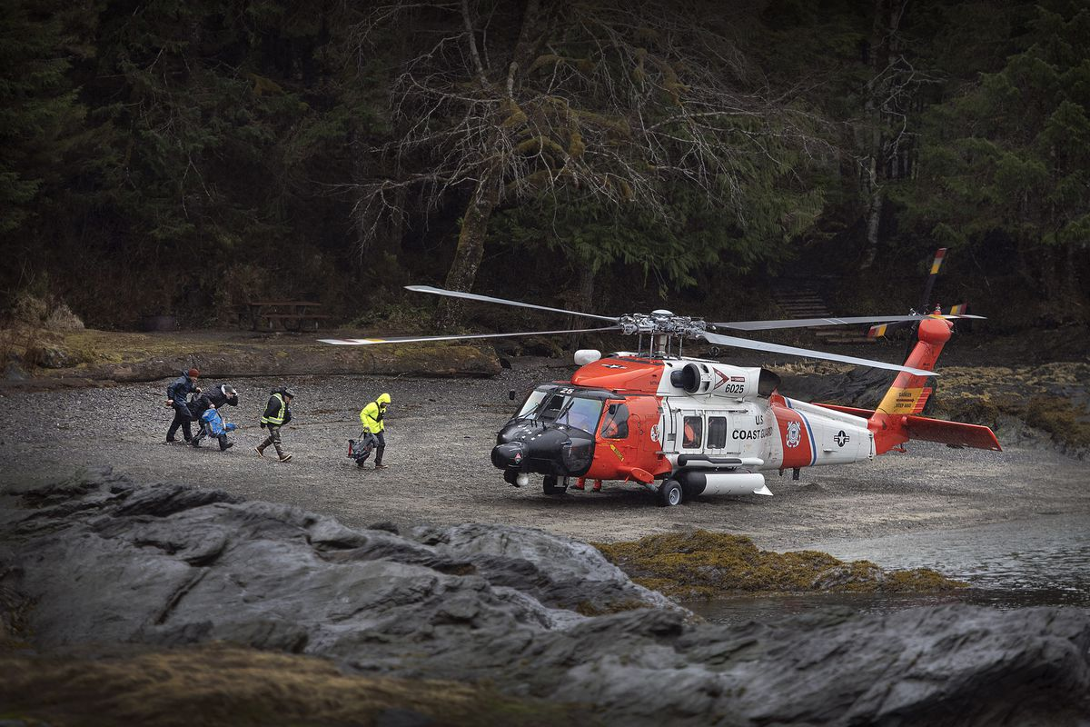 A U.S. Coast Guard helicopter sits in a beach area in order to airlift personnel with Ketchikan Volunteer Rescue Squad to a remote area of Lunch Creek in the search for a missing boy Saturday at a state recreation site in Ketchikan. (Dustin Safranek/Ketchikan Daily News via AP)