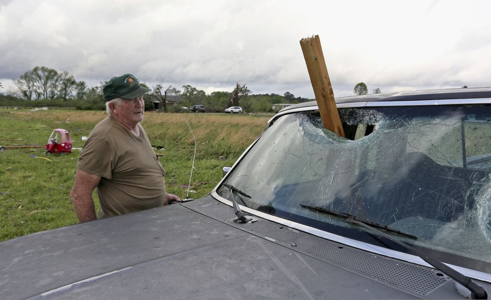 A man looks at a piece of wood that was blown through the windshield of his daughters truck in Hamilton, Miss., after a storm moved through the area Sunday, April 14, 2019. (AP Photo/Jim Lytle)