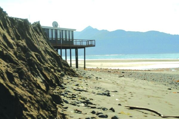 Buildings on stilts hover over an eroded bank on the Homer Spit on Sept. 11. Federal officials made stops around Southcentral Alaska to educate stakeholders on best practices for battling erosion either on the coasts or river banks. (Photo/Elizabeth Earl/For the Journal)