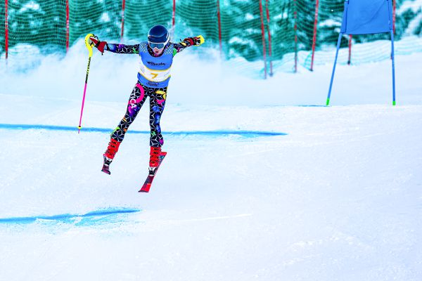 With a mixture of surprise and composure at being thrown into the air by the bump by the blue gate, Alyeska Ski Club U12 Alexandra Vonwalter-Gentner reaches to regain contact with the course in time to make the next gate in the second of two Alyeska Cup Super-Gs Thursday, Feb. 13, 2020. Despite her air time, she won both races, finishing in front of a pack of U14s. (Photo by Bob Eastaugh)
