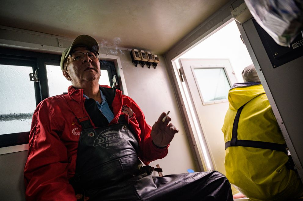 Nobuo Sugimura, 63, smokes a cigarette as he and other fishermen on the Hokushin Maru ship head back after catching salmon from the Sea of Okhotsk. (Photo for The Washington Post by Salwan Georges)