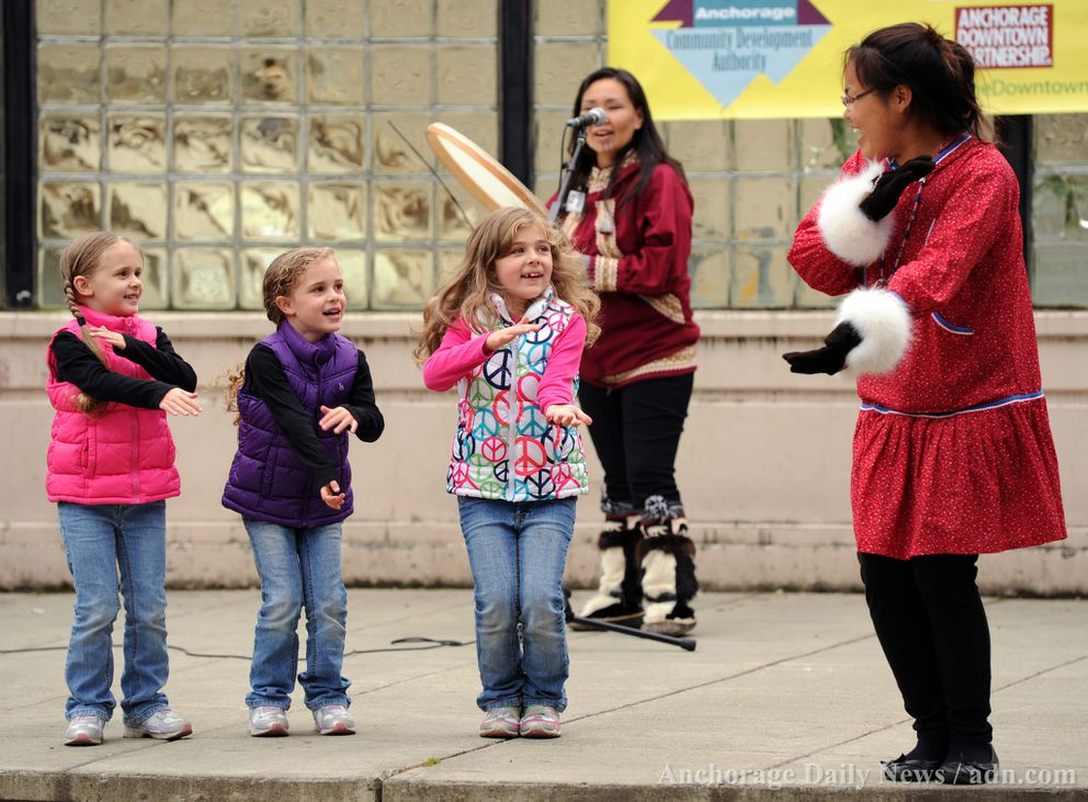 Siblings from left Kadee Farmer, 5, her twin Khloe, 5, and Kylee, 6, take the stage to learn some dance moves at an Alaska Native Heritage Center performance for Music in the Park Friday, July 5, 2013 downtown. Brandi Moore, right, led the youngsters as Yaari Kingeekuk drummed the beat. Brandi's twin sister Brittany also performed.