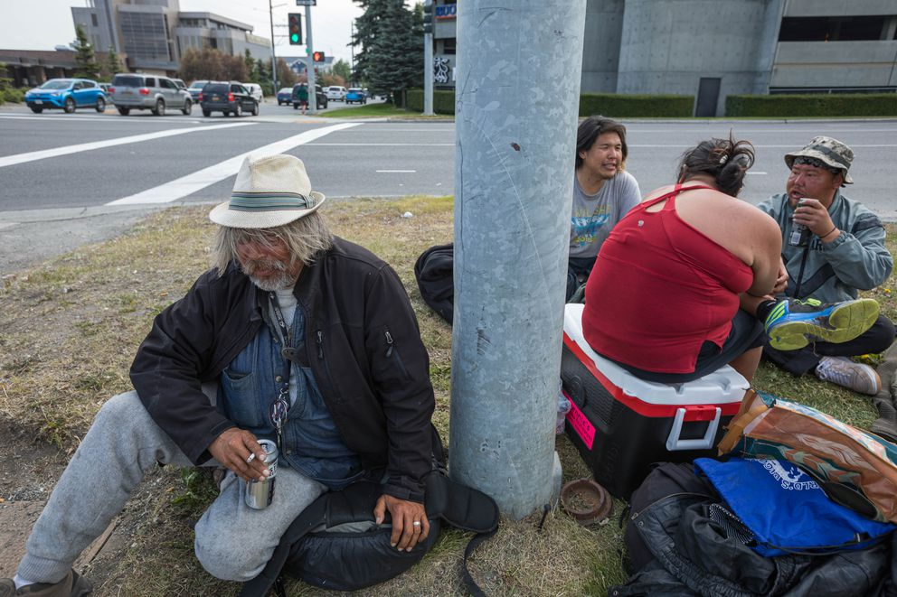 JR Voyles, left, drinks from a can of high-alcohol beer at an intersection in Midtown Anchorage Tuesday morning, June 25, 2019. He says that he's 'too beat up to work anymore. ' (Loren Holmes / ADN)