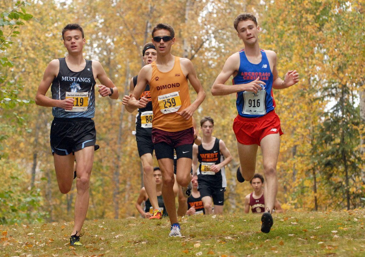 From left, Chugiak's Hyrum Nelson, Dimond's Sonny Prosser and Anchorage Christian's Tristian Merchant run together nearly the start of the boys varsity race at the Bartlett State Preview Cross Country Meet on Saturday. Prosser set a course record by winning the race in 15 minutes, 6.2 seconds. (Matt Tunseth / ADN)