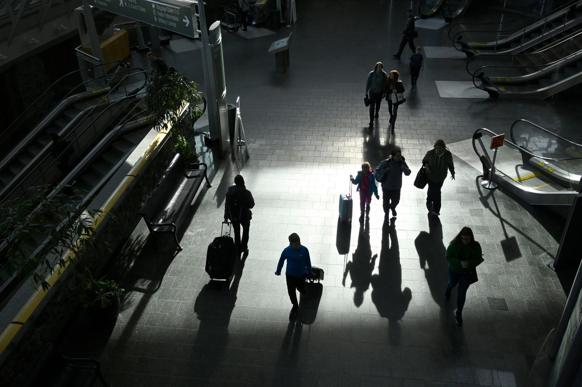 Travelers walk through Ted Stevens Anchorage International Airport on March 13, 2020. (Marc Lester / ADN)