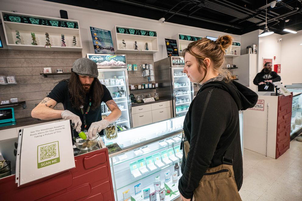Cannabis sales associate Justin Benner helps Ashley Straight with her order at Raspberry Roots, a cannabis retail store, on Thursday, March 19, 2020. The store is limiting the number of people it allows inside at the same time so that everyone can maintain a safe distance apart. Straight purchased 1/8 oz of Lemonade bud and 1 gram of Fruity Pebbles sugar wax. (Loren Holmes / ADN)