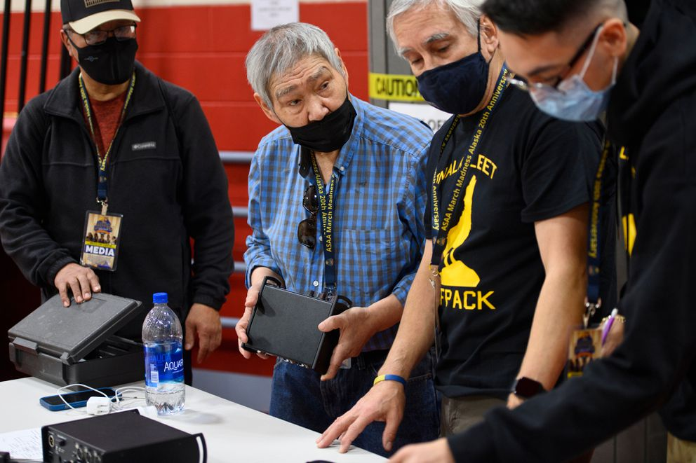 KCUK station manager Peter Tuluk, second from left, talks with other broadcasters from Unalakleet at Wasilla High School. Tuluk has been broadcasting basketball coverage in Cup'ik for 35 years. (Marc Lester / ADN)