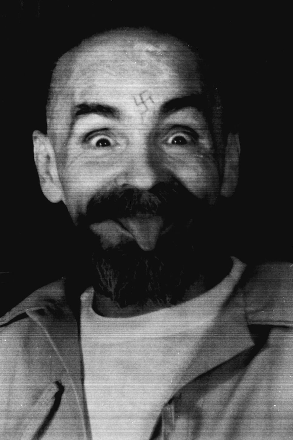 Charles Manson clowns around as he is led to his cell upon the conclusion of his exclusive interview with Reuters August 25, 1989. REUTERS/File