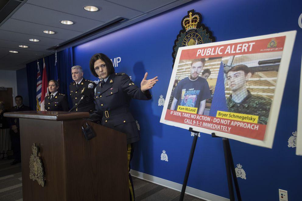 Royal Mounted Police Sgt. Janelle Shoihet gestures toward security camera images of Kam McLeod, 19, and Bryer Schmegelsky, 18, displayed during a conference in Surrey, British Columbia, Tuesday, July 23, 2019. The two young men, thought to be missing, are now suspects in the murders of an American woman and her Australian boyfriend as well as the death of another man in northern British Columbia, Canadian police said Tuesday. (Darryl Dyck/The Canadian Press via AP)