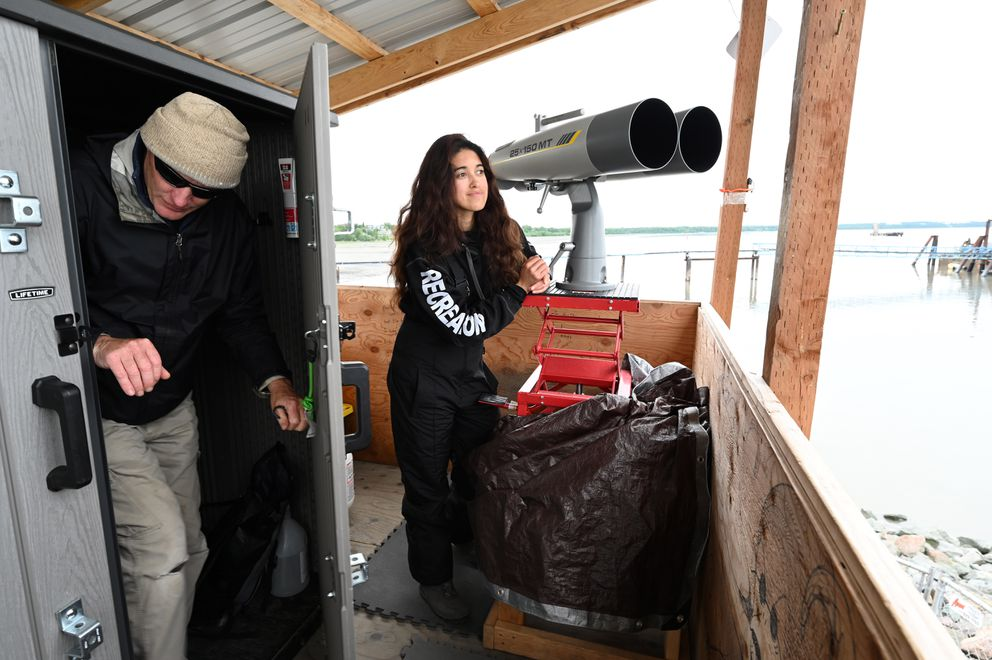 Duncan Allen ducks out of the data room at a monitoring station at the mouth of Ship Creek as Arika Garcia keeps her eyes trained on the waters of the Knik Arm. (Anne Raup / ADN)
