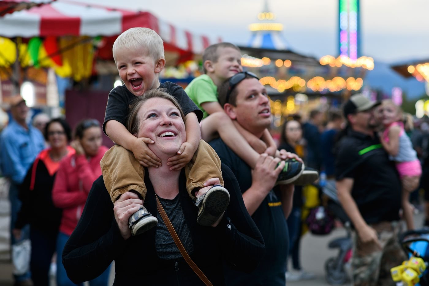 Lindsey Noll holds Wyatt Noll, 2, as they watch riders on the 1001 Nachts ride. David Noll holds Sawyer Noll, 5, at right. (Marc Lester / ADN)