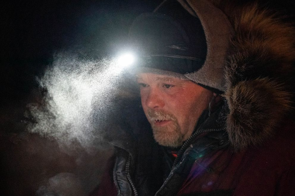 Aaron Burmeister walks through his team before leaving Takotna early Thursday after completing his 24-hour layover (Loren Holmes / ADN)