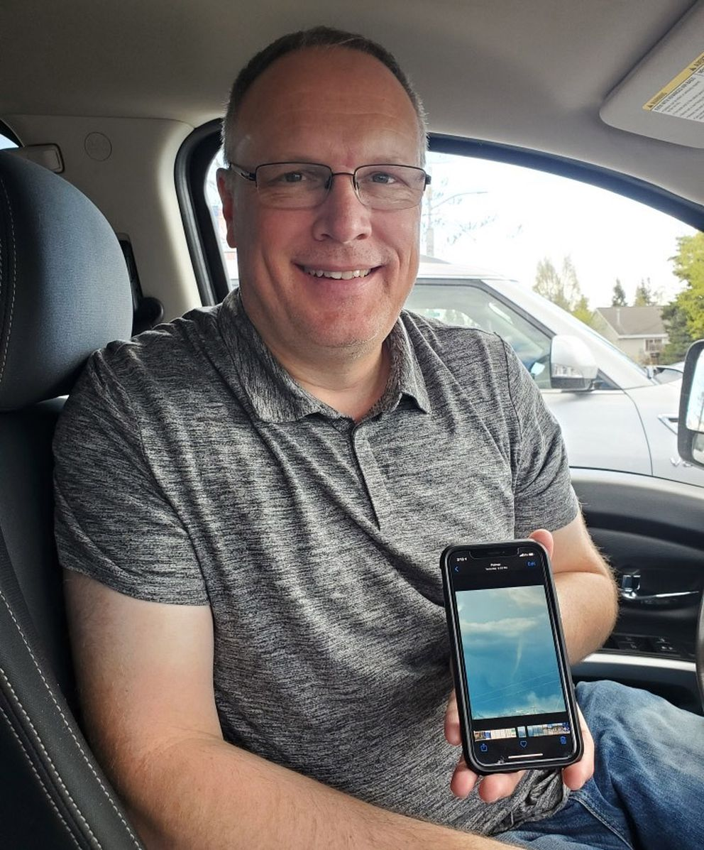 Robert Warren holds his phone with a photo of a funnel cloud that developed over Palmer at 6:55 p.m. May 13, 2021. (Photo provided by Robert Warren)