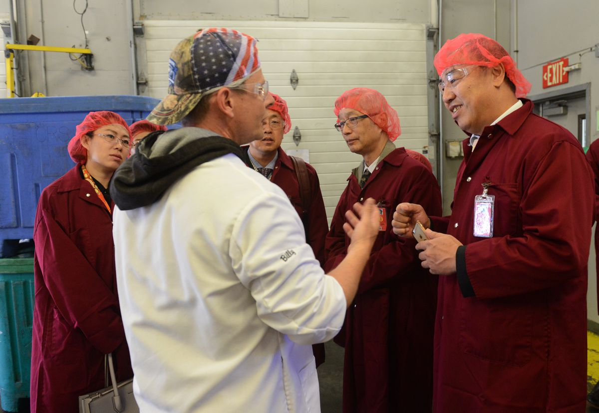 Billy Green, general manager of the Copper River Seafoods Anchorage plant, talks with Ming Sun, director of the World Trade Center in Harbin, China, during a tour of the seafood plant in Anchorage on Friday. (Bob Hallinen / ADN)