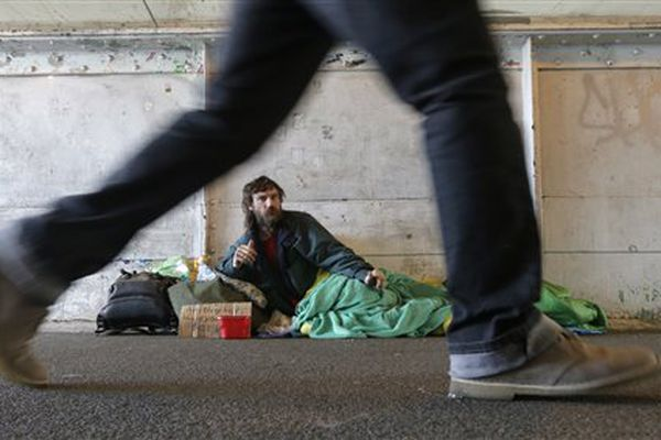 Harold McDuffie II, who says he has been homeless for three years, watches pedestrians pass by as he lies in a sleeping bag on a bridge leading to the ferry dock in downtown Seattle on Tuesday, Feb. 9, 2016. Seattle has the third-highest number of homeless people in the U.S.