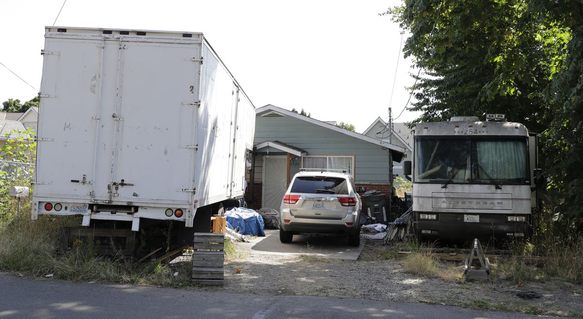 Vehicles are parked outside the home of Paige A. Thompson, who uses the online handle