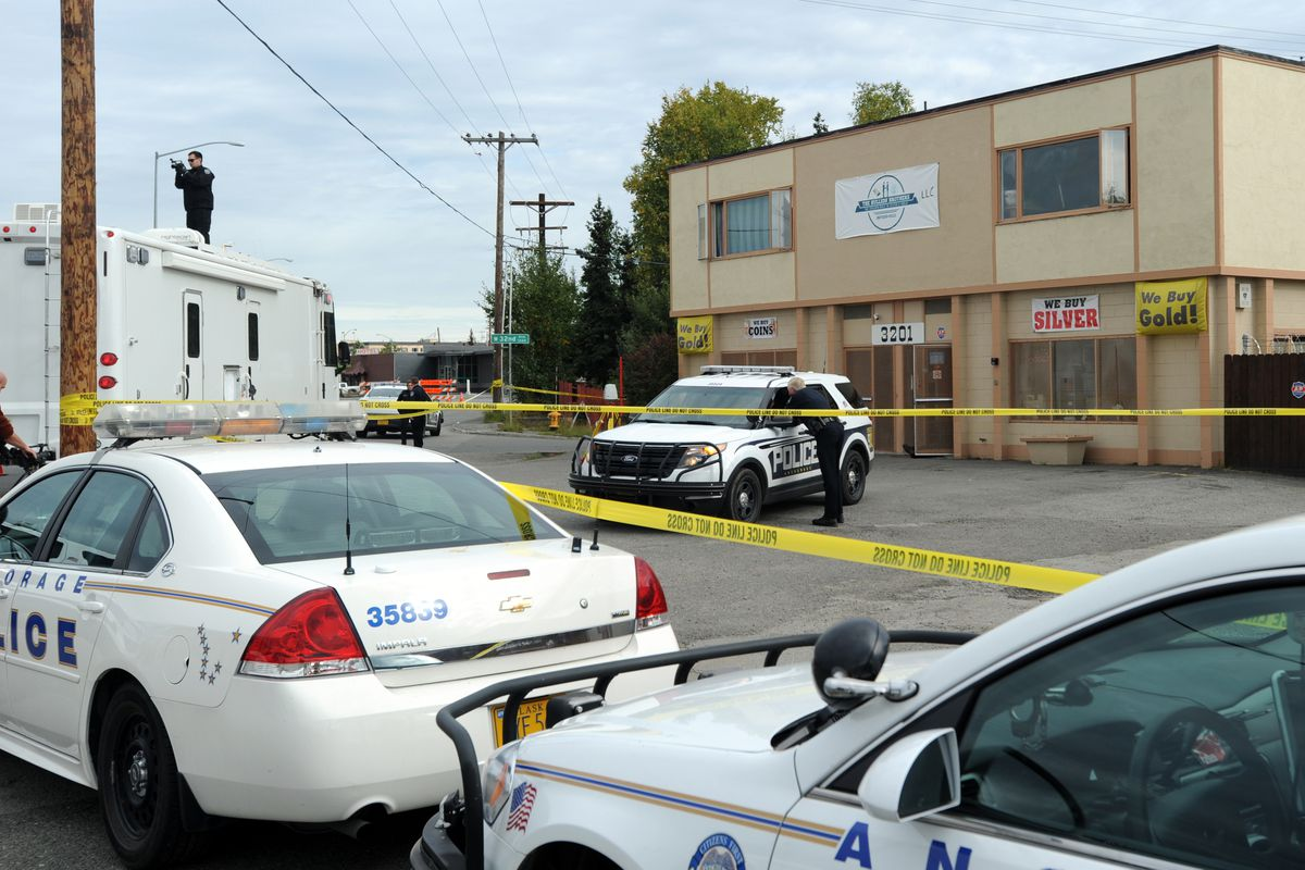 Crime Scene Team officer Jeff Elbie, left, records the scene of a triple homicide shooting at The Bullion Brothers gold shop on Sept. 12, 2017, in Spenard. (Erik Hill / ADN archive)