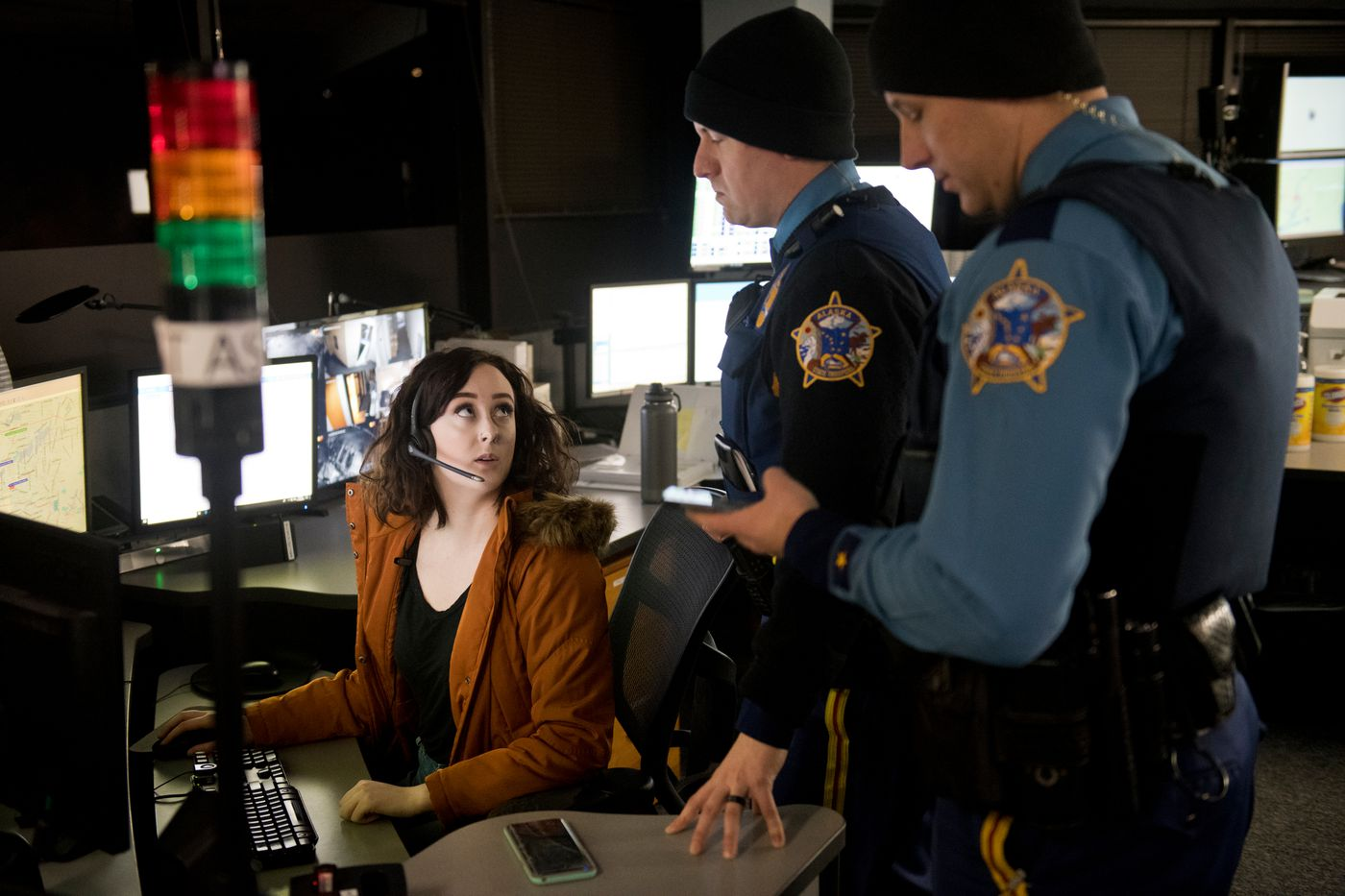 Megan Sidders, left, dispatcher for Mat-Com Dispatch in Wasilla, talks with Alaska State Troopers Fred Parker, center, and Ryan Anderson on November 18, 2019. (Marc Lester / ADN)