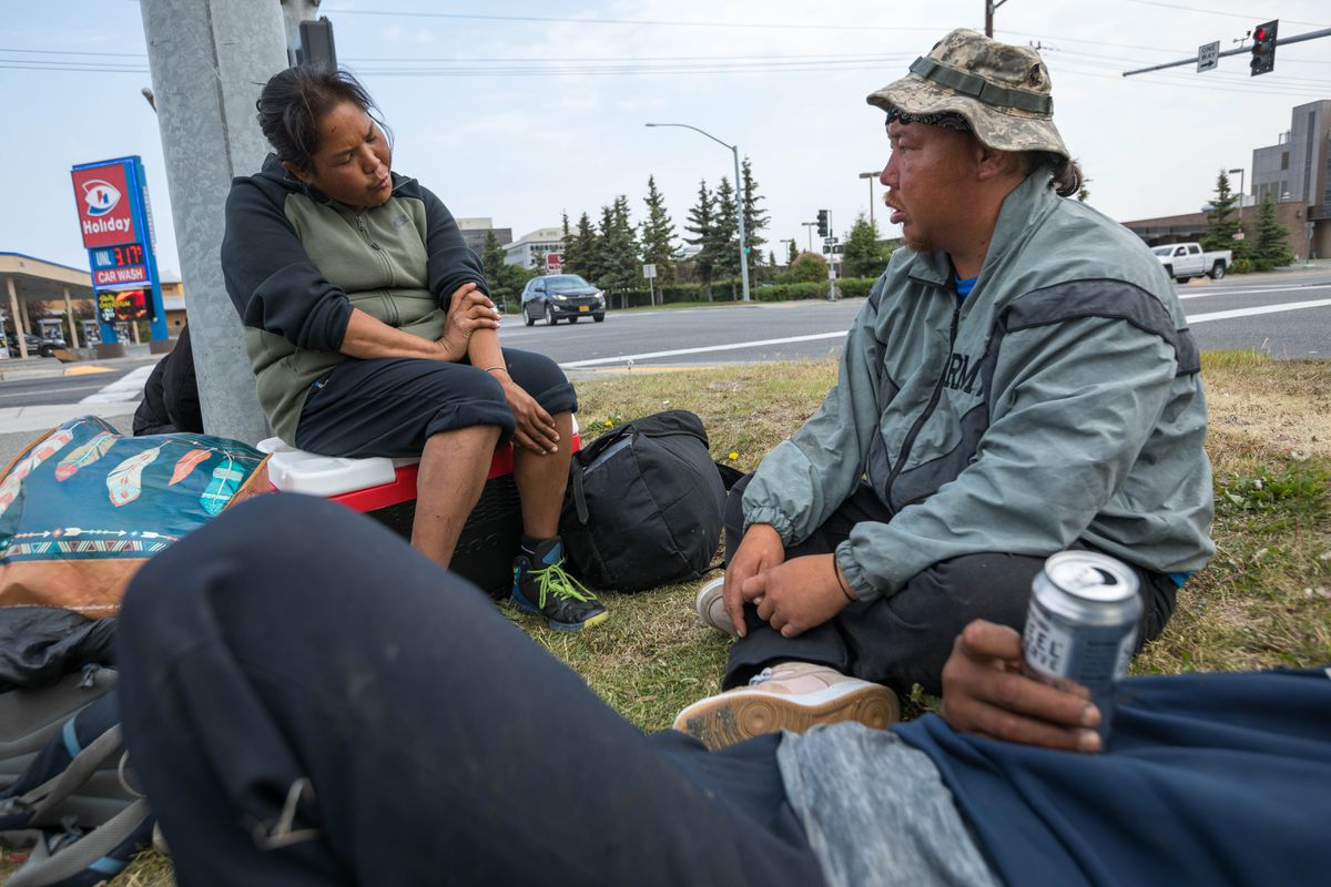 Sara Ondola-Carter, her husband Tony Carter, and a friend pass around a can of high-alcohol beer at an intersection in Midtown Anchorage Tuesday morning, June 25, 2019. The couple said they met outside of Fred Meyer and had been married about a year.