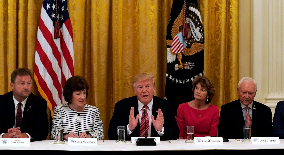 President Donald Trump meets with Senate Republicans about health care in the East Room of the White House on Tuesday. Trump is flanked by Sen. Susan Collins of Maine, left, and Sen. Lisa Murkowski of Alaska. REUTERS / Kevin Lamarque