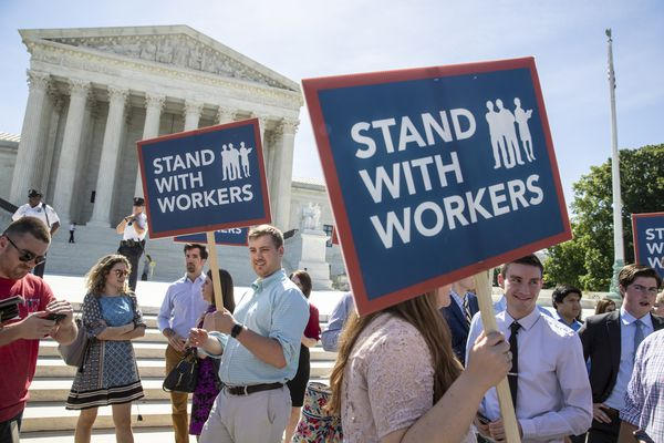 In this Monday, June 25, 2018 photo, people gather at the Supreme Court awaiting a decision in an Illinois union dues case, Janus vs. AFSCME, in Washington. The Supreme Court says government workers can't be forced to contribute to labor unions that represent them in collective bargaining, dealing a serious financial blow to organized labor. (AP Photo/J. Scott Applewhite)