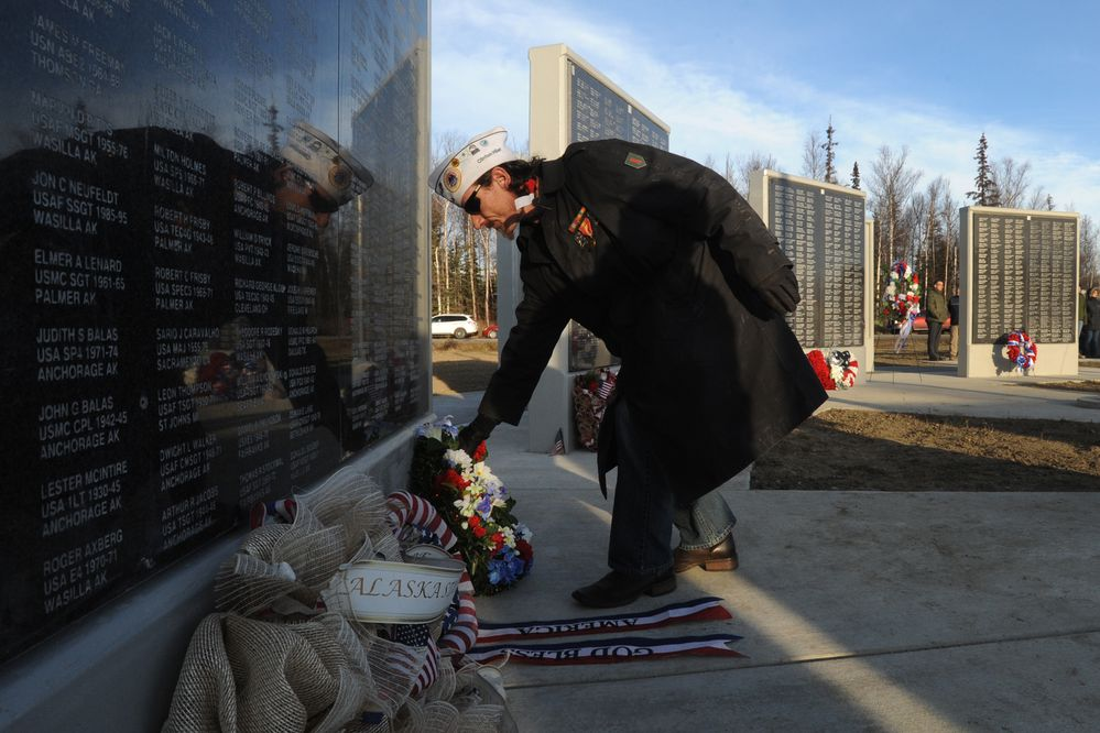 U.S. Army veteran Clinton Hiler, commander of AMVEST Post 11, places a wreath at the Veterans Wall of Honor during a Veterans Day ceremony in Wasilla on Monday, Nov. 11, 2019. (Bill Roth / ADN)