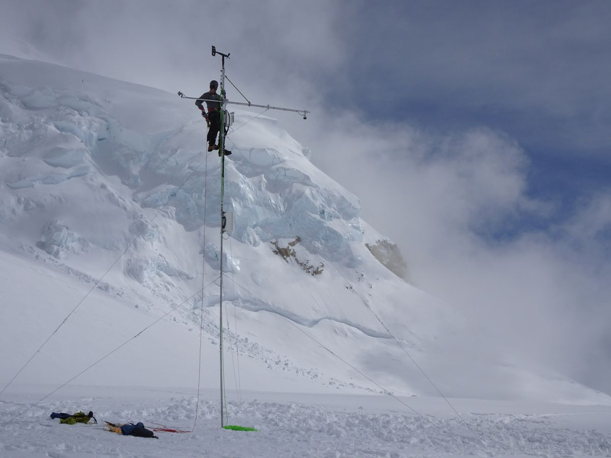 Tucker Chenoweth tests the 14,000-foot weather station on the Kahiltna Glacier. (Photo by Michael Loso)