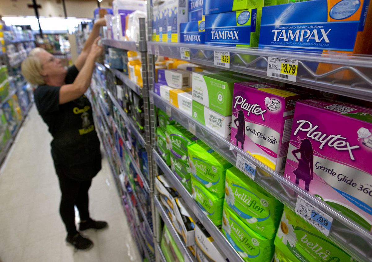 Tammy Compton restocks tampons at Compton's Market, in Sacramento, Calif. (AP Photo/Rich Pedroncelli, File)