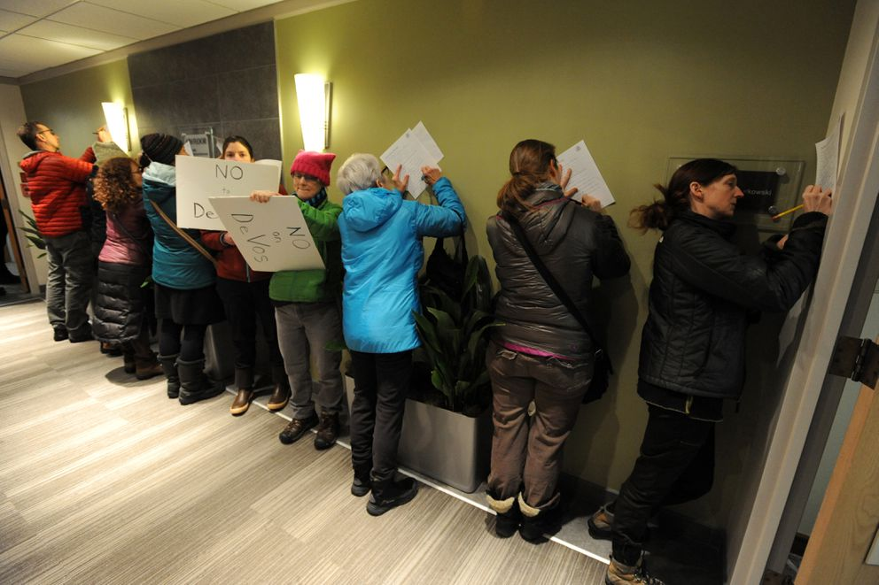 "Activists fill out ""Public Opinion Message"" forms outside the Anchorage office of U.S. Sen. Lisa Murkowski urging her to oppose the nomination of Betsy DeVos. (Bill Roth / Alaska Dispatch News)"