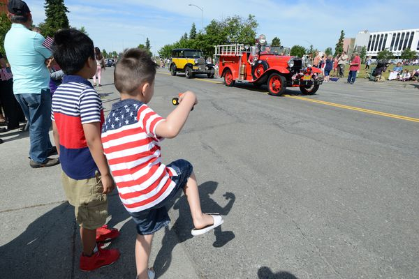 James Eribal, 8, and Aaron Tanner, 5, admire the old vehicles driving by in Anchorage's Fourth of July parade, 2018. (Anne Raup / ADN)