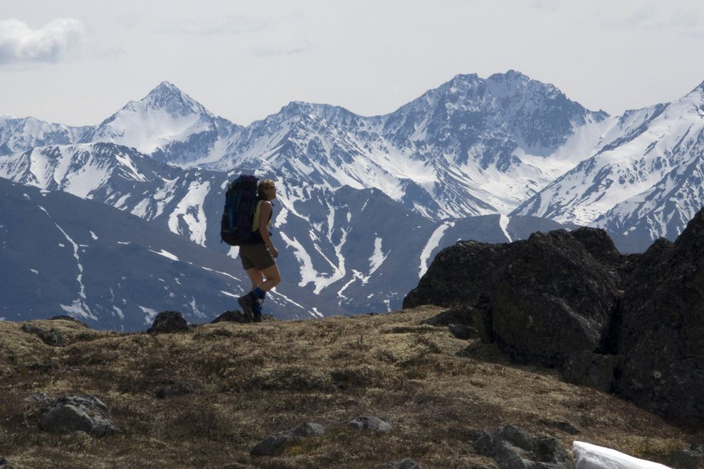 A backpacker descends the trails above Eska Falls in the Talkeetna Mountains outside of Sutton. The Chugach Range is in the background. (Richard J. Murphy / ADN)