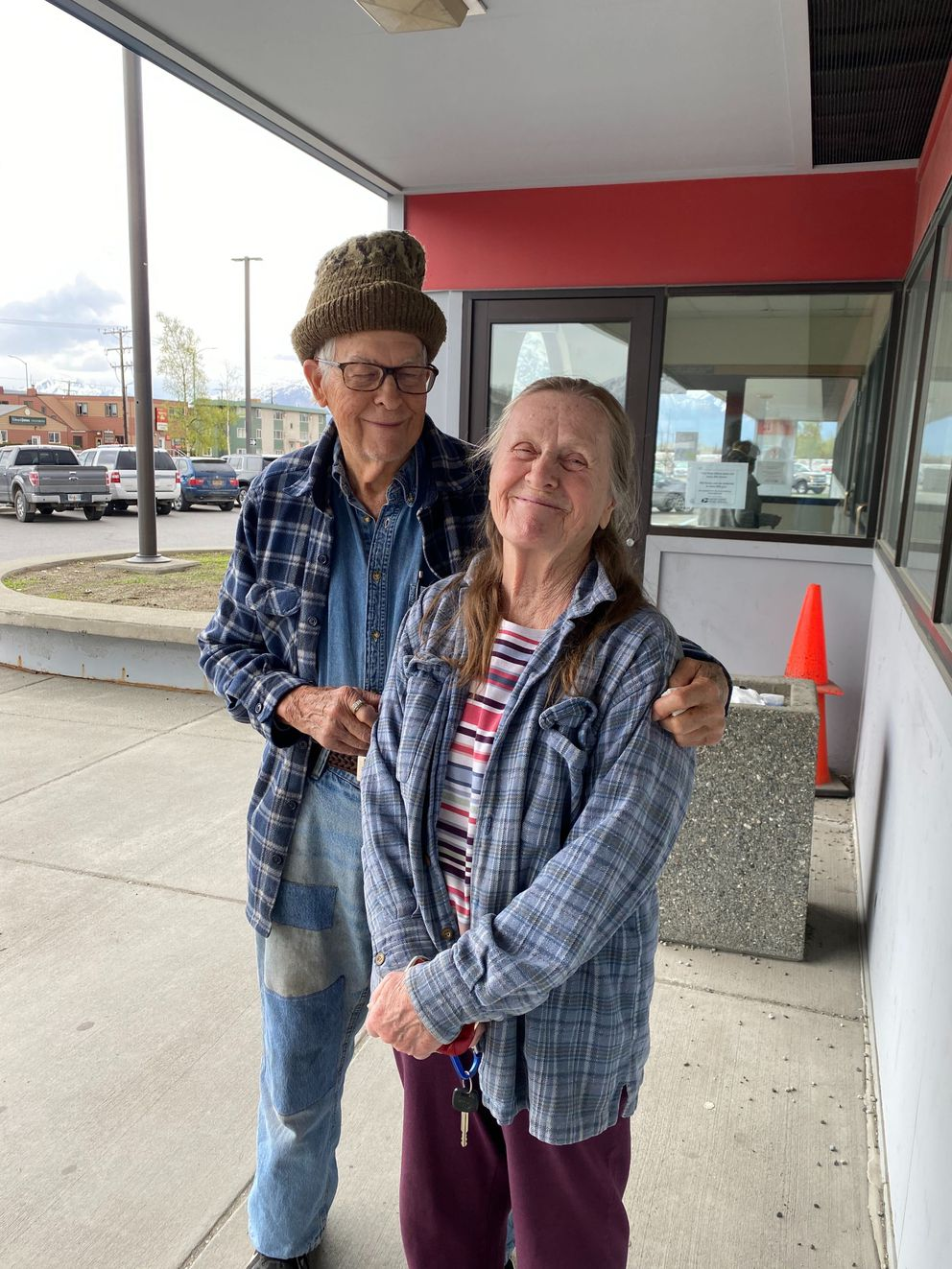 Kenneth Cowart and Sue Houser photographed outside Palmer's post office on Monday, May 11 2020. Houser says she doesn't wear a face mask because she's not afraid of getting COVID-19. Cowart wore a mask but moved it to play harmonica as the couple waited in a long line inside. (Zaz Hollander / ADN)