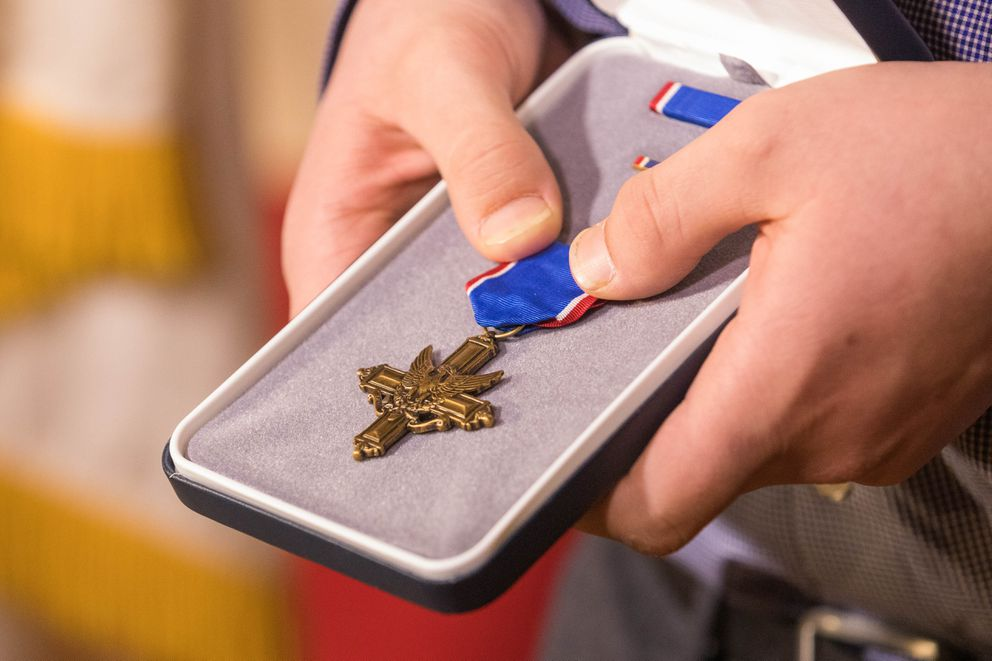 MacAiden Gallegos holds his father's Distinguished Service Cross on Saturday. Staff Sgt. Justin Gallegos was posthumously awarded the nation's second-highest award for valor for actions he took during the 2009 Battle of Kamdesh in Afghanistan. (Loren Holmes / ADN)