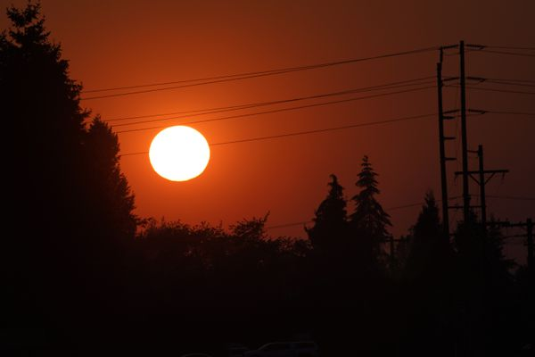 The sun is seen against a sky turned orange with smoke from wildfires as it sets, Tuesday, Sept. 8, 2020, near Sumner, Wash., south of Seattle. (AP Photo/Ted S. Warren)