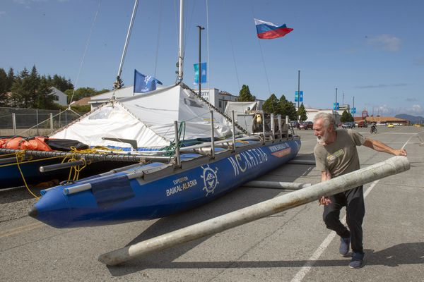 In this Thursday, Aug. 28, 2019 photo, a Russian sailor visiting Sitka aboard another sailboat places pipes under the Russian inflatable catamaran sailboat Iskatel as it is is towed by skipper Anatoly Kazakevich to a spot on the parking lot near the University of Alaska campus in Sitka, Alaska. The boat is on a multi-year expedition from Lake Baikal in Siberia to Alaska. (James Poulson/The Daily Sitka Sentinel via AP)