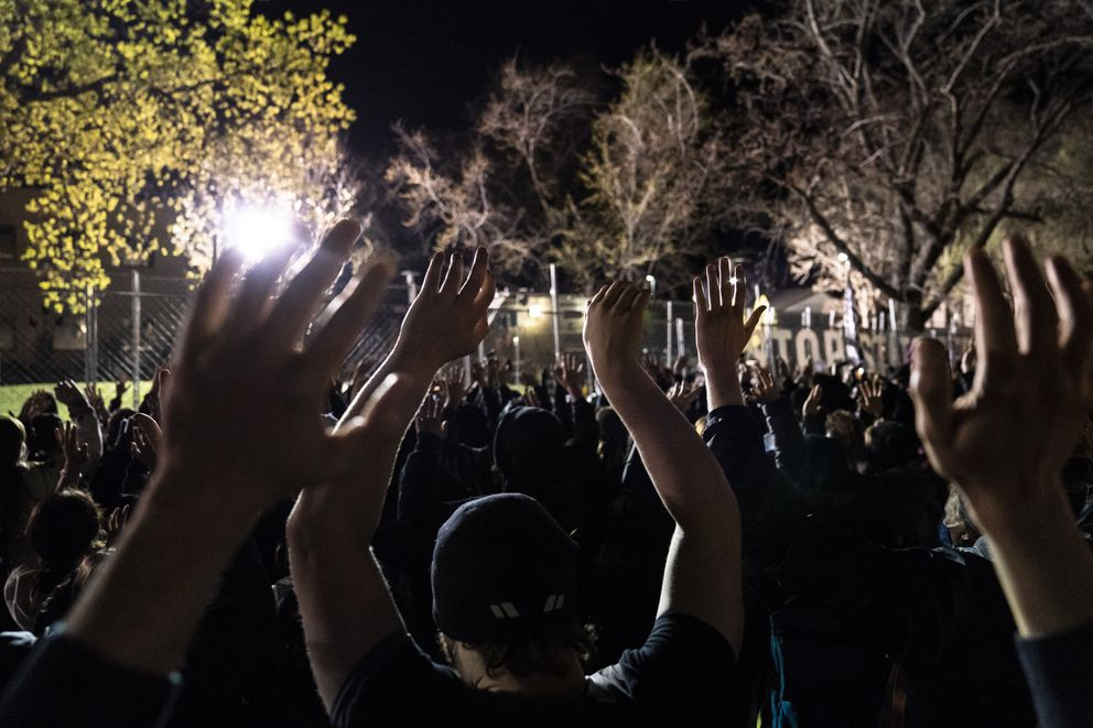 Demonstrators hold their hands up toward authorities stationed behind a perimeter security fence, during a protest over the fatal shooting of Daunte Wright by a police officer during a traffic stop, outside the Brooklyn Center Police Department, Saturday, April 17, 2021, in Brooklyn Center, Minn. (AP Photo/John Minchillo)