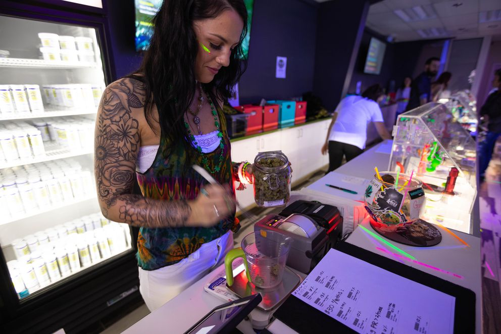 Budtender Jerriann Kruger weighs a gram of Tirich Mir for a customer at Cannabaska on Friday, April 20, 2018. Tirich Mir is an indica strain of marijuana with a high THC content of nearly 24%. (Loren Holmes / ADN)
