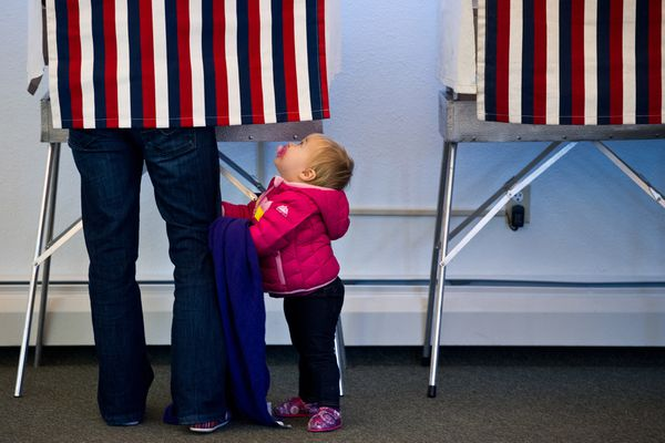 One-year-old Zoe Buck looks up to her mother Julie Buck in the voting booth at the Alaska Zoo on Election Day, Tuesday, November 4, 2014.