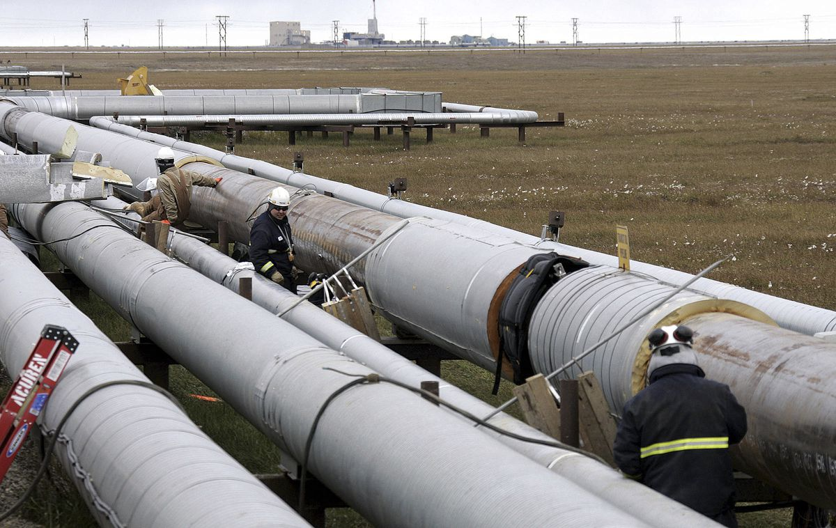 FILE - In this Aug. 18, 2006 file photo BP workers, in the background, remove insulation from an oil transit pipeline at the Prudhoe Bay oil field on Alaska's North Slope. BP, a major player on Alaska's North Slope for decades, is selling all of its assets in the state, the company announced Tuesday, Aug. 27, 2019. Hilcorp Alaska is purchasing BP interests in both the Prudhoe Bay oil field and the trans-Alaska pipeline for $5.6 billion, BP announced in a release. (AP Photo/Al Grillo)