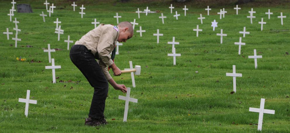 In preparation for Memorial Day, Boy Scout Kevin Martin with Troop 125 helped American Legion Jack Henry Post 1 place about 2,500 crosses on veterans' gravesites at Anchorage Memorial Park Cemetery on Sunday, May 24, 2020. Post Commander Michael Downs said placing the crosses is 'a way we can remember and honor our veterans, especially those who didn't come back.' (Bill Roth / ADN)