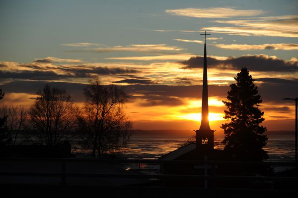 The sun sets behind the Chapel by the Sea overlooking Turnagain Arm in south Anchorage, Alaska on Saturday, Dec. 23, 2017. (Bob Hallinen / ADN)