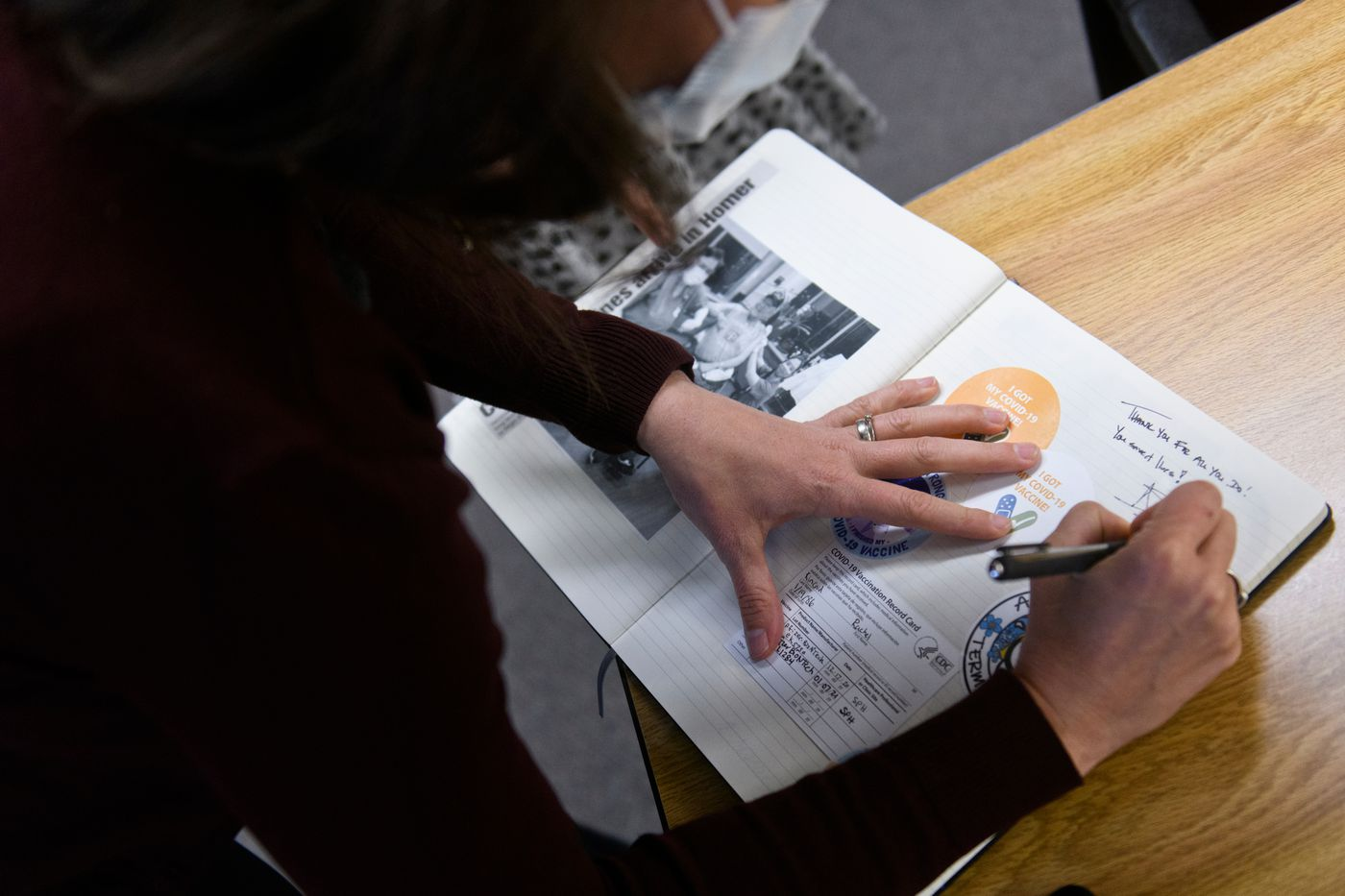 Zink signs a scrapbook for Rachael Kincaid, a nurse practitioner. 'You saved lives, ' Zink wrote. (Marc Lester / ADN)