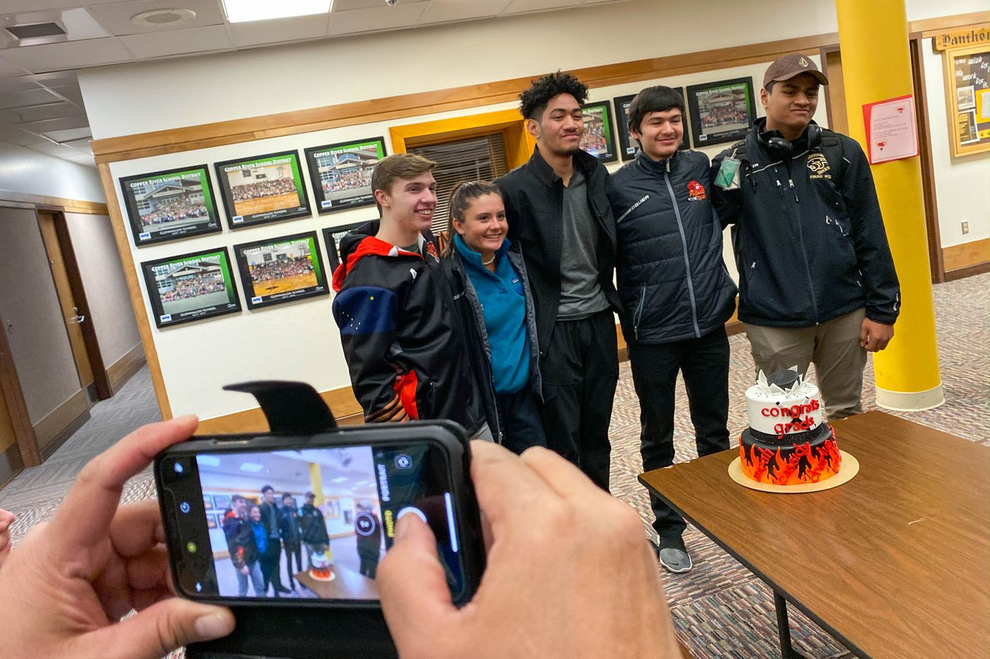 Toa Finau takes a picture of Alaska Heat seniors, from left, Micah Serino, Cassidy Matthews, Charlie Taui, Richard Charlie and Aisake Finau, during the Senior Night ceremony. Matthews and Finau are from Glennallen, Serino and Taui are from Utqiagvik and Charlie is from Tok. (Loren Holmes / ADN)