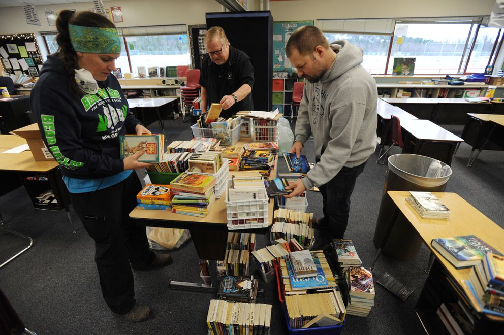 Bear Valley Elementary 6th grade teacher Elizabeth Stadnicky, left, gets helps sorting through water damaged books from Spring Hill Elementary 6th grade teachers Rick Wien and Marco Christian on Wednesday, Dec. 5, 2018, as they get the school ready to open next Monday. (Bill Roth / ADN)