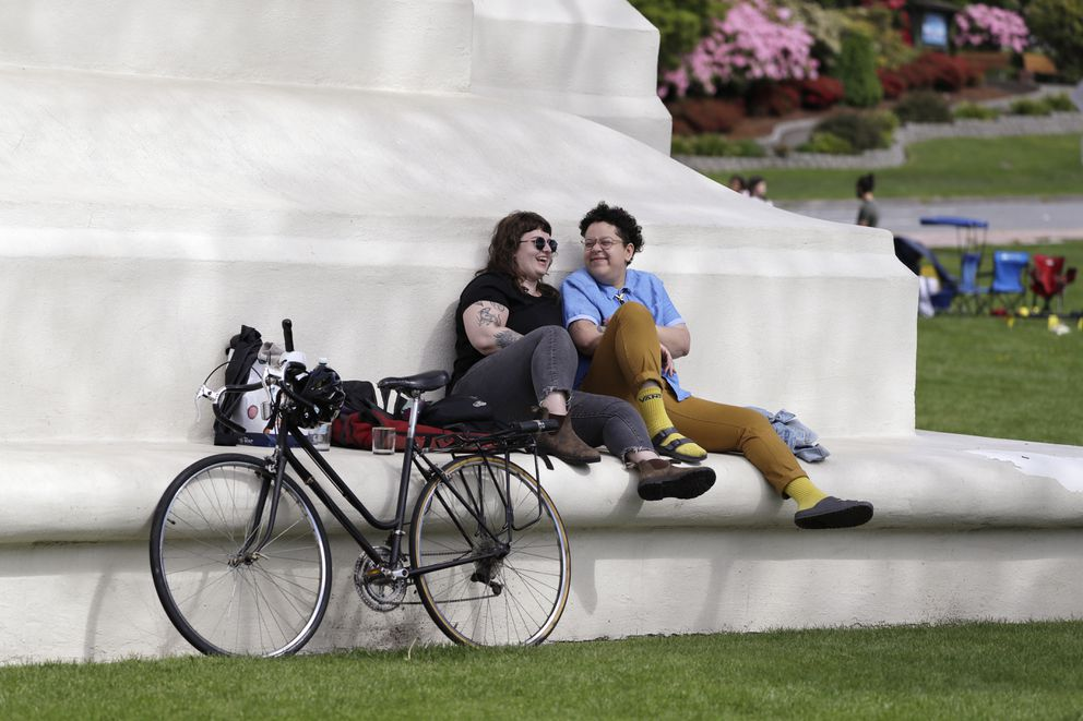 In this photo taken May 17, 2020, sweethearts Hannah Smith, left, of Vancouver, British Columbia, and Jabree Robinson, of Bellingham, Wash., sit on the base of the Peace Arch. (AP Photo/Elaine Thompson)
